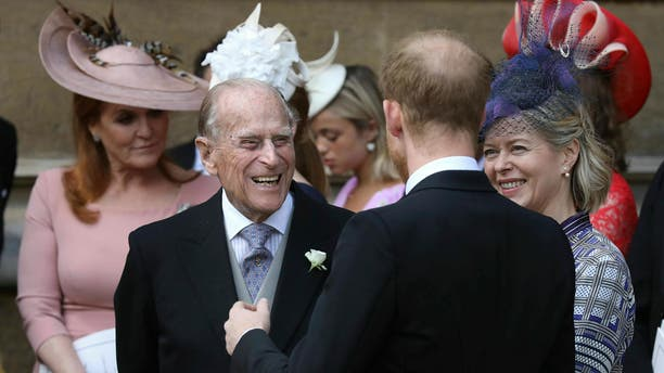 Prince Philip talks to Prince Harry, right, as they leave after the wedding of Lady Gabriella Windsor and Thomas Kingston at St George's Chapel, Windsor Castle, near London, England, Saturday, May 18, 2019. (Steve Parsons/Pool via AP)