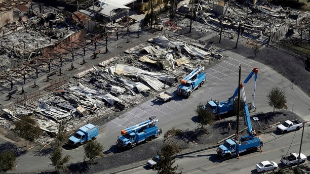 In 2017, PG&E crews work on restoring power lines in a fire-ravaged neighborhood in an aerial view in the aftermath of a wildfire in Santa Rosa, Calif. (AP Photo/Marcio Jose Sanchez, File)