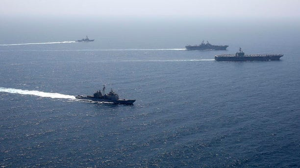 In this photo released by the U.S. Navy, the Abraham Lincoln Carrier Strike Group and Kearsarge Amphibious Ready Group conduct joint operations in the U.S. 5th Fleet area of operations over the weekend.