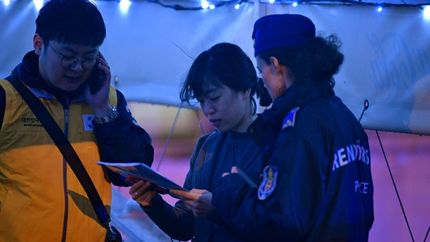 South Korean Embassy personnel help identifying the victims of an accident during a search operation for survivors on the River Danube in downtown Budapest, Hungary, Thursday, May 30, 2019. (Zsolt Szigetvary/MTI via AP)