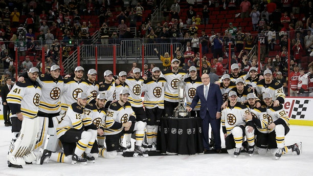Boston Bruins players pose with the Prince of Wales trophy and Bill Daly, deputy commissioner of the National Hockey League, following Game 4 of the NHL hockey Stanley Cup Eastern Conference finals against the Carolina Hurricanes in Raleigh, N.C., on Thursday. Boston won 4-0 to advance to the Stanley Cup Final. (Associated Press)