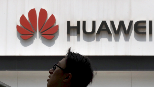 In this photo taken Thursday, May 16, 2019, a man past by a Huawei store in Beijing. Google is assuring users of Huawei smartphones the American company's services still will work on them following U.S. government restrictions on doing business with the Chinese tech giant. (AP Photo/Ng Han Guan)