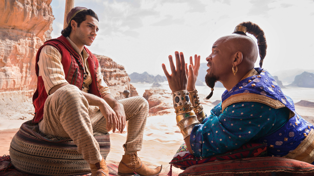 """This image released by Disney shows Mena Massoud as Aladdin, left, and Will Smith as Genie in Disney's live-action adaptation of the 1992 animated classic """"Aladdin."""""""