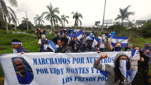 Anti-government protesters, some wearing masks to hide their identity from authorities, protest on the grounds of the Cathedral after their march was blocked by police in Managua, Nicaragua, Sunday, May 26, 2019. The banner features Eddy Montes Praslin, a Nicaraguan-American dual national who was a staunch opponent of the government of President Daniel Ortega and who died in a prison disturbance in Nicaragua. (AP Photo/Alfredo Zuniga)
