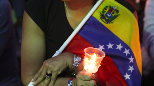 An opponent to Venezuela's President Nicolas Maduro holds a candle during a vigil for those killed in street fighting over the past week in Caracas, Venezuela, Sunday, May 5, 2019. Opposition leader Juan Guaid called in vain for a military uprising to overthrow President Nicolas Maduro, and five people were killed in clashes between protesters and police. (AP Photo/Martin Mejia)