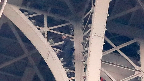 A climber is pictured between two iron columns of the Eiffel Tower while a rescue worker is partially seen at right, Monday, May 20, 2019 in Paris. (AP Photo/Michel Euler)