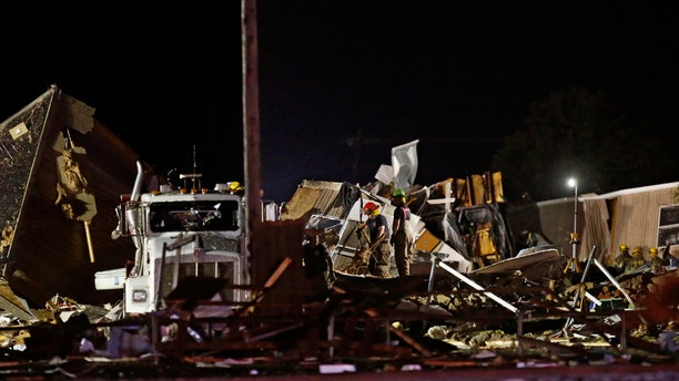 Emergency workers search through debris from a mobile home park, Sunday, May 26, 2019, in El Reno, Ok.