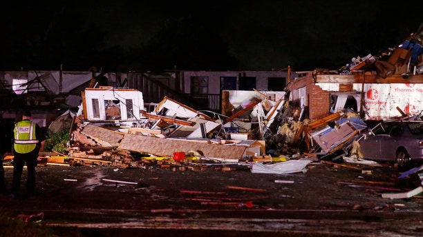 Police stand at the ruins of a hotel in El Reno, Okla., Sunday, May 26, 2019, following a tornado touchdown late Saturday night.