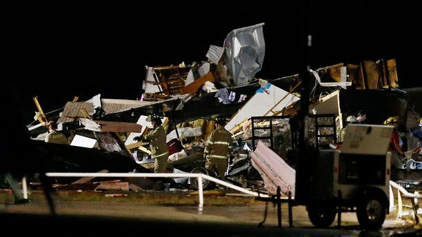 Emergency workers search through debris from a mobile home park, Sunday, May 26, 2019, in El Reno, Ok., following a tornado touchdown late Saturday night.
