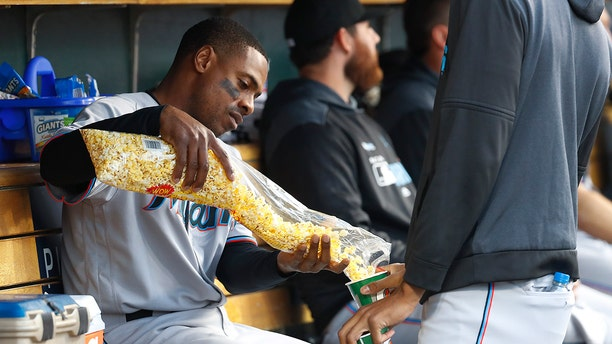 Miami Marlins' Curtis Granderson, left, shares popcorn with a teammate in the dugout during the third inning of the team's baseball game against the Detroit Tigers in Detroit, Tuesday, May 21, 2019. (AP Photo/Paul Sancya)