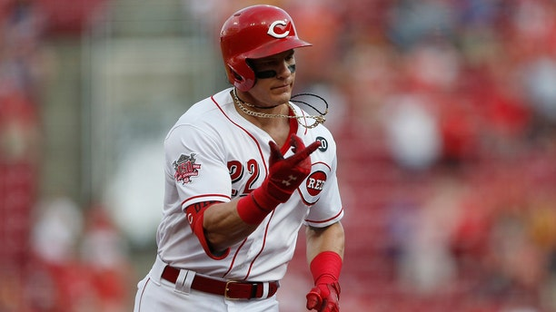 Cincinnati Reds' Derek Dietrich (22) points as he rounds the bases with a two-run home run off Pittsburgh Pirates starting pitcher Jordan Lyles during the fourth inning of a baseball game, Tuesday, May 28, 2019, in Cincinnati. (AP Photo/Gary Landers)