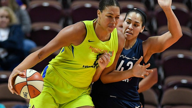 Dallas Wings' Liz Cambage, left, drives against Connecticut Sun's Brionna Jones during a preseason WNBA basketball game in Uncasville, Conn. (AP Photo/Jessica Hill, File)