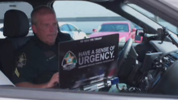 Pasco County Sheriff's Corporal Alan Wilkett uses his laptop from his service vehicle.