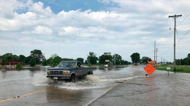A pickup truck evacuates from an area in north Jefferson City Missouri as floodwaters from the Missouri River rise over the road on Friday, May 24, 2019. The flooding come as residents are still cleaning up from a powerful tornado that hit the state's capital city on May 22. (AP Photo/David A. Lieb)