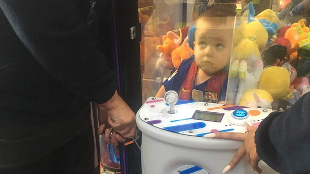 A mother-of-three was left in hysterics after finding her son Noah, pictured, had climbed into a toy arcade machine in hopes of nabbing a teddy bear.
