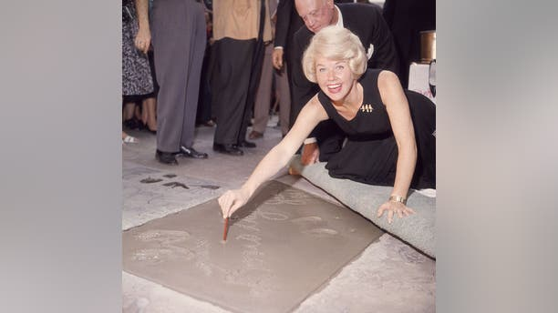 American singer and actress Doris Day signs her name in cement by her handprints on Jan. 19, 1961 on Hollywood Boulevard. (Photo by Hulton Archive/Getty Images)