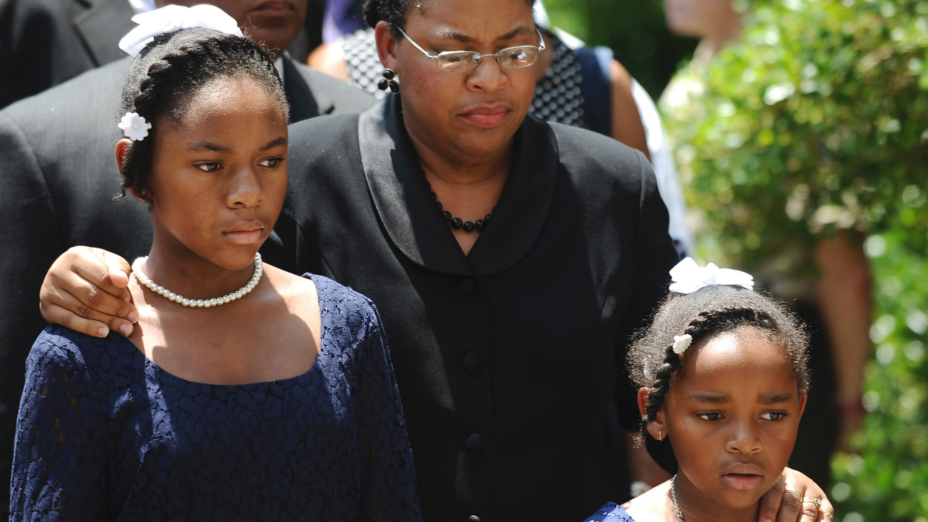 FILE - In this June 24, 2015, file photo Sen. Clementa Pinckney's wife Jennifer Pinckney, center, and her daughters, Eliana, left, and Malana, right, follow his casket into the South Carolina Statehouse in Columbia, S.C. The Rev. Clementa Pinckney, was one of the nine killed by Dylann Roof, who sat through 45 minutes of Bible study at the church before firing shots. Pinckney and her daughter, Malana, were in the late reverend's office when they heard gun shots in another room. (AP Photo/Rainier Ehrhardt, File)