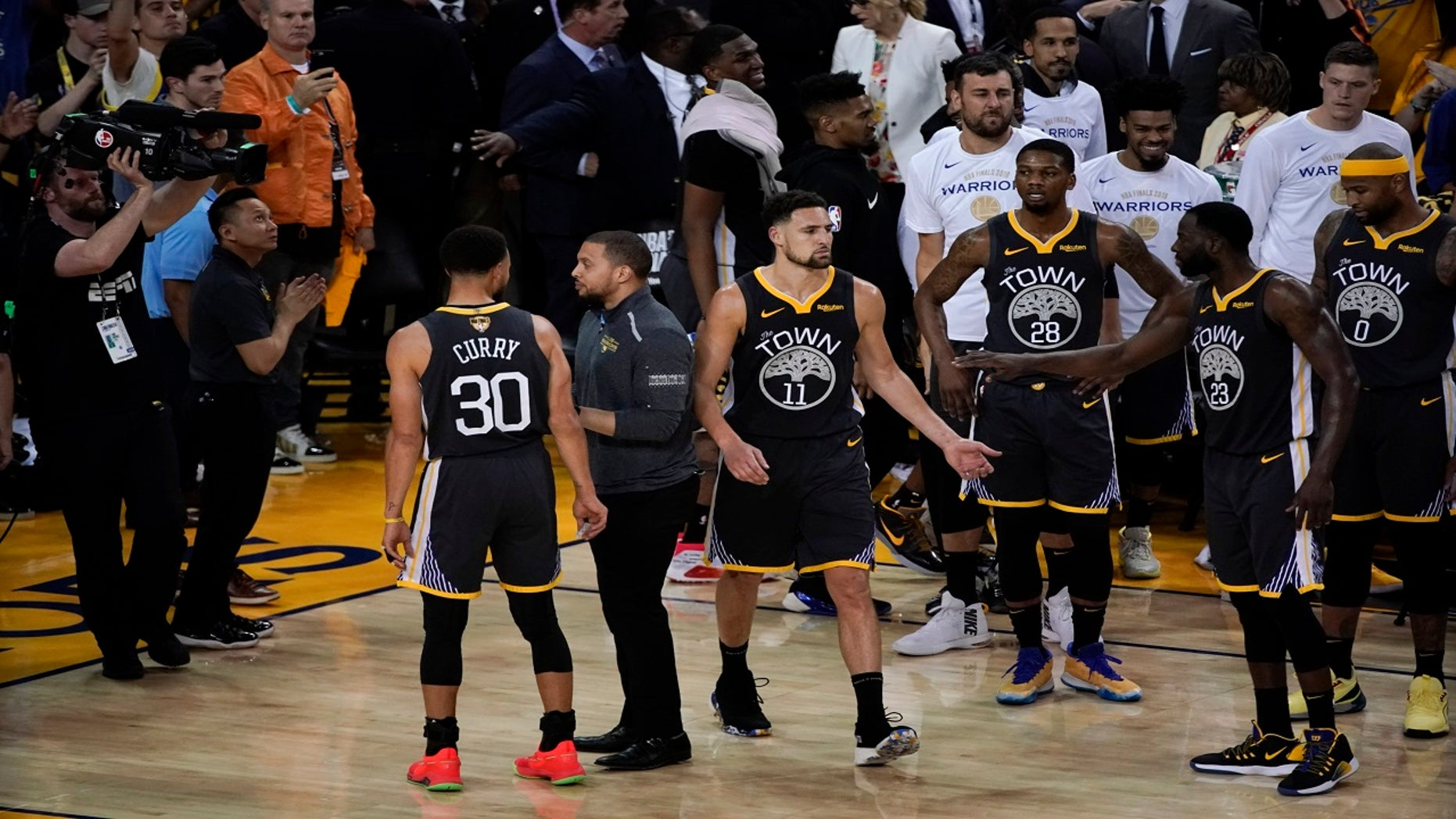 Golden State Warriors guard Klay Thompson (11) is greeted by teammates after walking back onto the court to shoot free throws after an injury against the Toronto Raptors during the second half of Game 6.