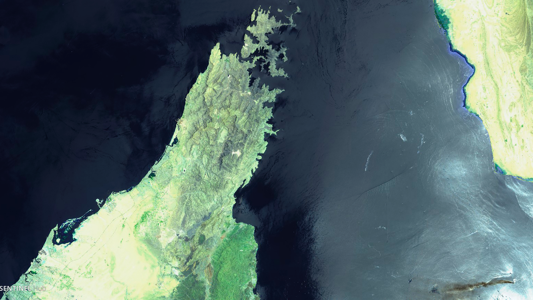 This June 13, 2019 false-color image from the European Commission's Sentinel-2 satellite that was processed by Sinergise's Sentinel Hub website shows the Norwegian-owned MT Front Altair, bottom right, ablaze with smoke rising from it in the Gulf of Oman after what the U.S. described as a limpet mine attack by Iran. Iran has denied being involved in the incident. The land mass to the left is the United Arab Emirates and Oman on the Arabian Peninsula. The land mass in the upper right hand corner is Iran. (European Commission via AP)