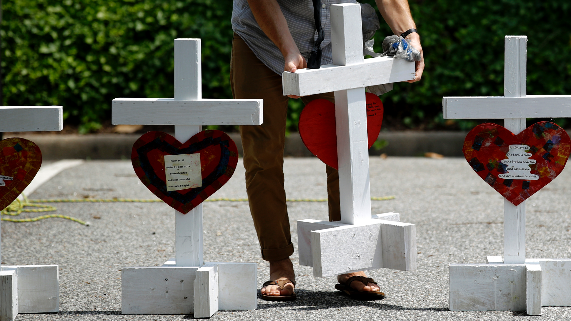 FILE - In this June 2, 2019, file photo, a volunteer prepares to place crosses for victims of a mass shooting at a municipal building in Virginia Beach, Va., at a nearby makeshift memorial. Police responding to the deadly mass shooting were unable to confront the gunman at one point because they didn't have the key cards needed to open doors on the second floor. Whether the delay contributed to the death toll is unclear, but the episode illustrated how door-lock technology that is supposed to protect people can hamper police and rescue workers in an emergency. (AP Photo/Patrick Semansky, File)