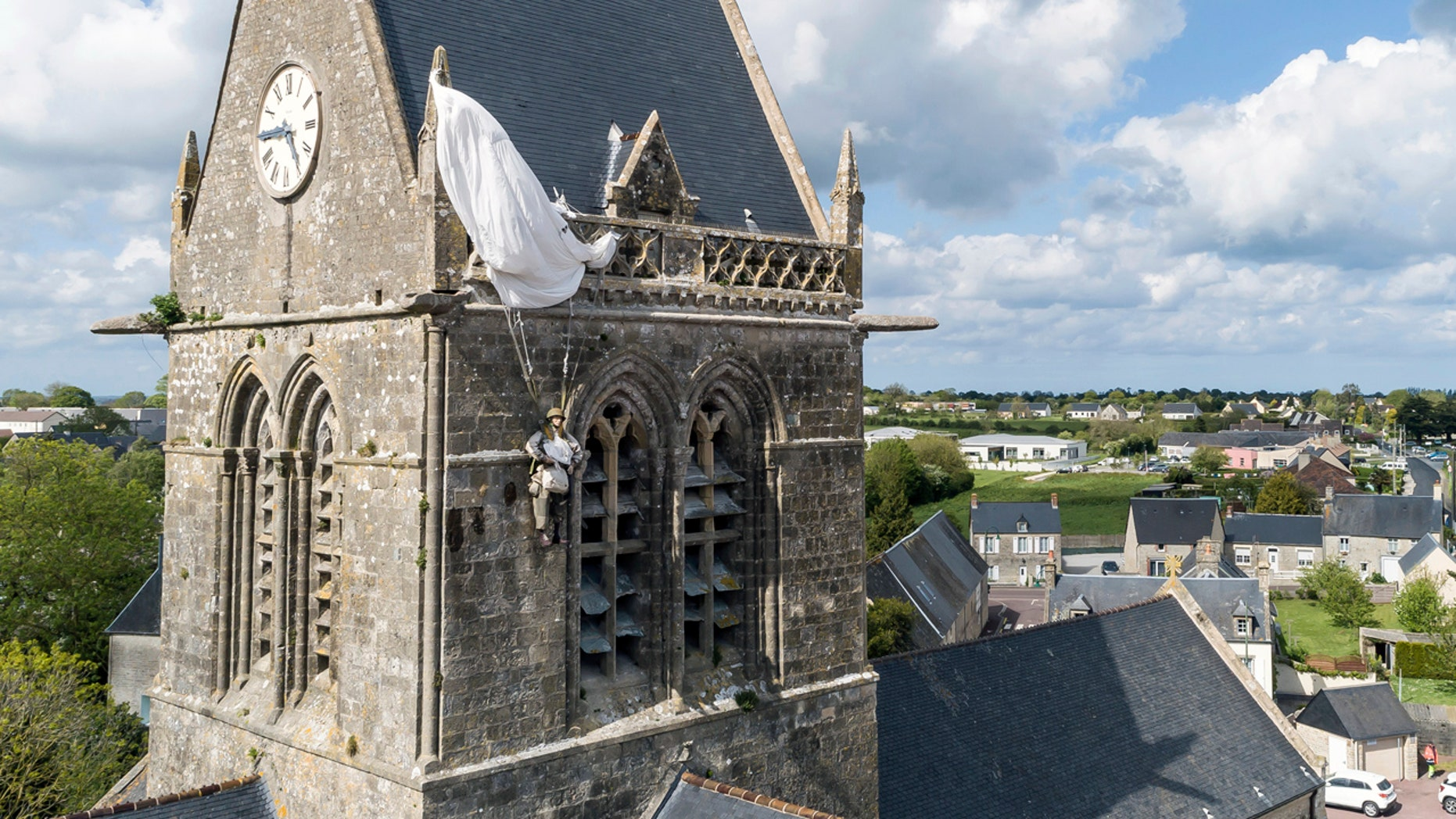 In this photo taken with a drone, a dummy paratrooper representing a WWII paratrooper from the 82nd Airborne hangs on the bell tower of the church of Sainte Mere Eglise, in Normandy, France, Thursday, May 9, 2019. Seventy-five years ago, American paratrooper John Steele dangled from a clock tower in Sainte-Mere-Eglise after his parachute got caught during the D-Day invasion, and survived. (AP Photo/David Vincent)