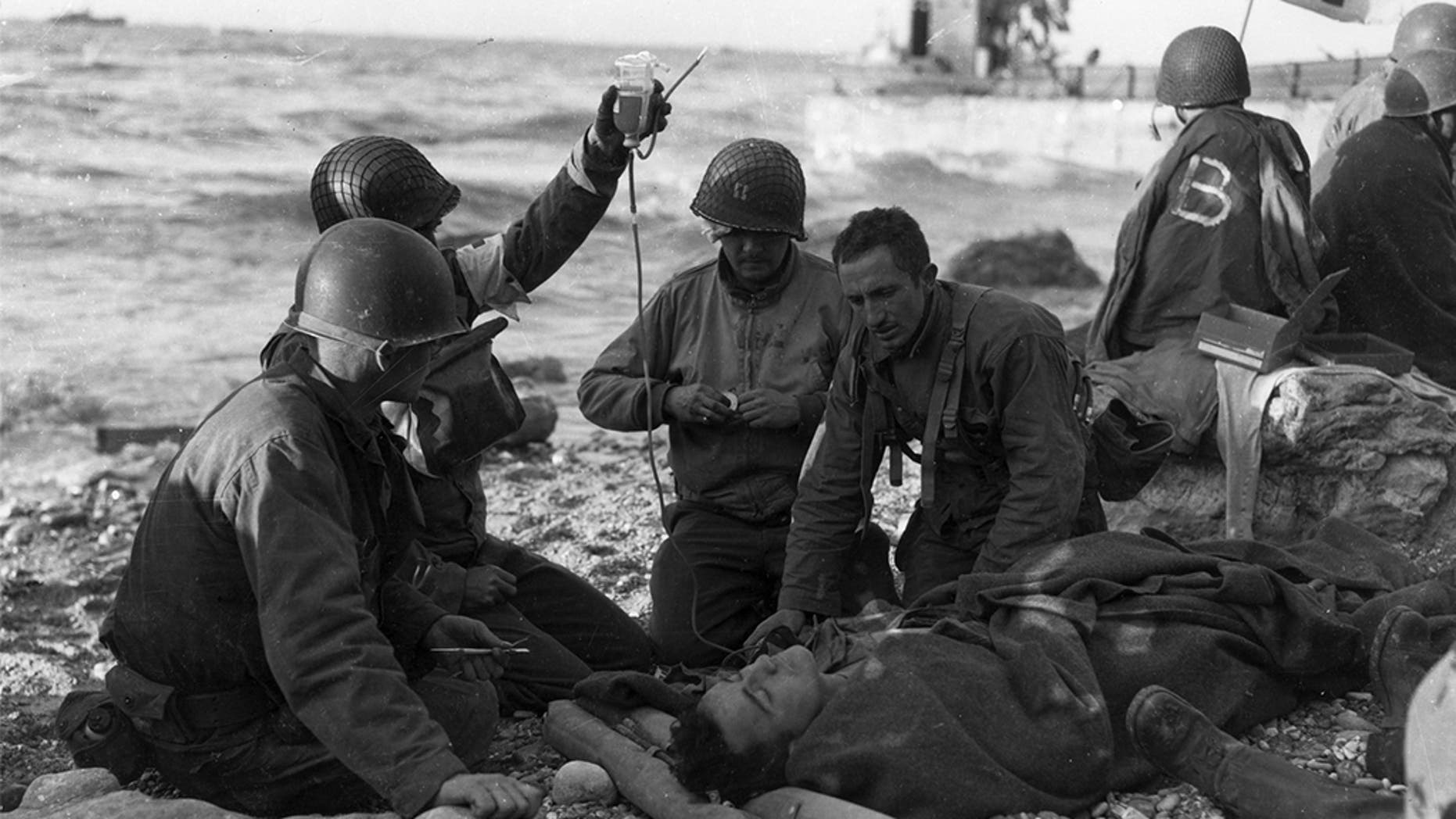 FILE -- June 12, 1944: American medics administer a plasma transfusion to a survivor of a landing craft sunk off the coast of northern France. (Photo by Weintraub/MPI/Getty Images)