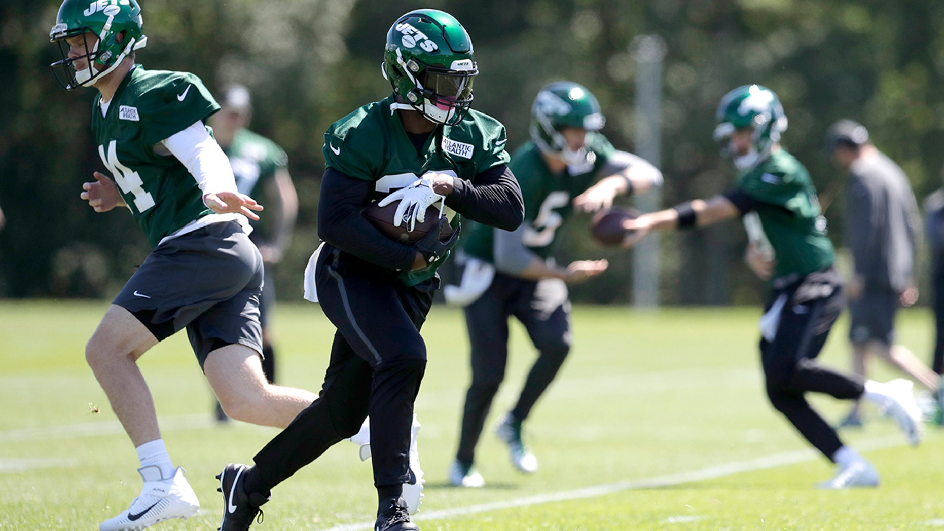New York Jets quarterback Sam Darnold, left, hands off to running back Le'Veon Bell while running a drill at the team's NFL football training facility in Florham Park, N.J., Tuesday, June 4, 2019. (AP Photo/Julio Cortez)