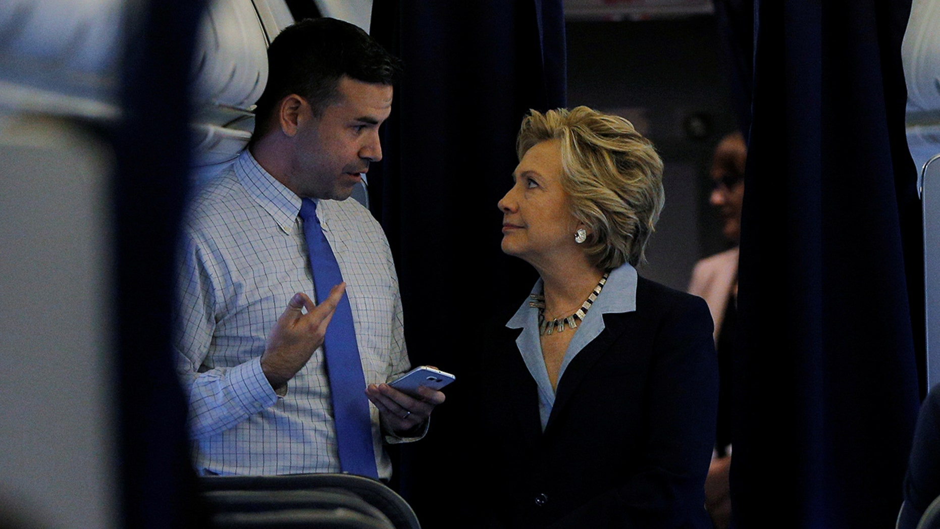 Hillary Clinton and national press secretary Brian Fallon talking onboard her campaign plane in White Plains, New York, in October 2016.