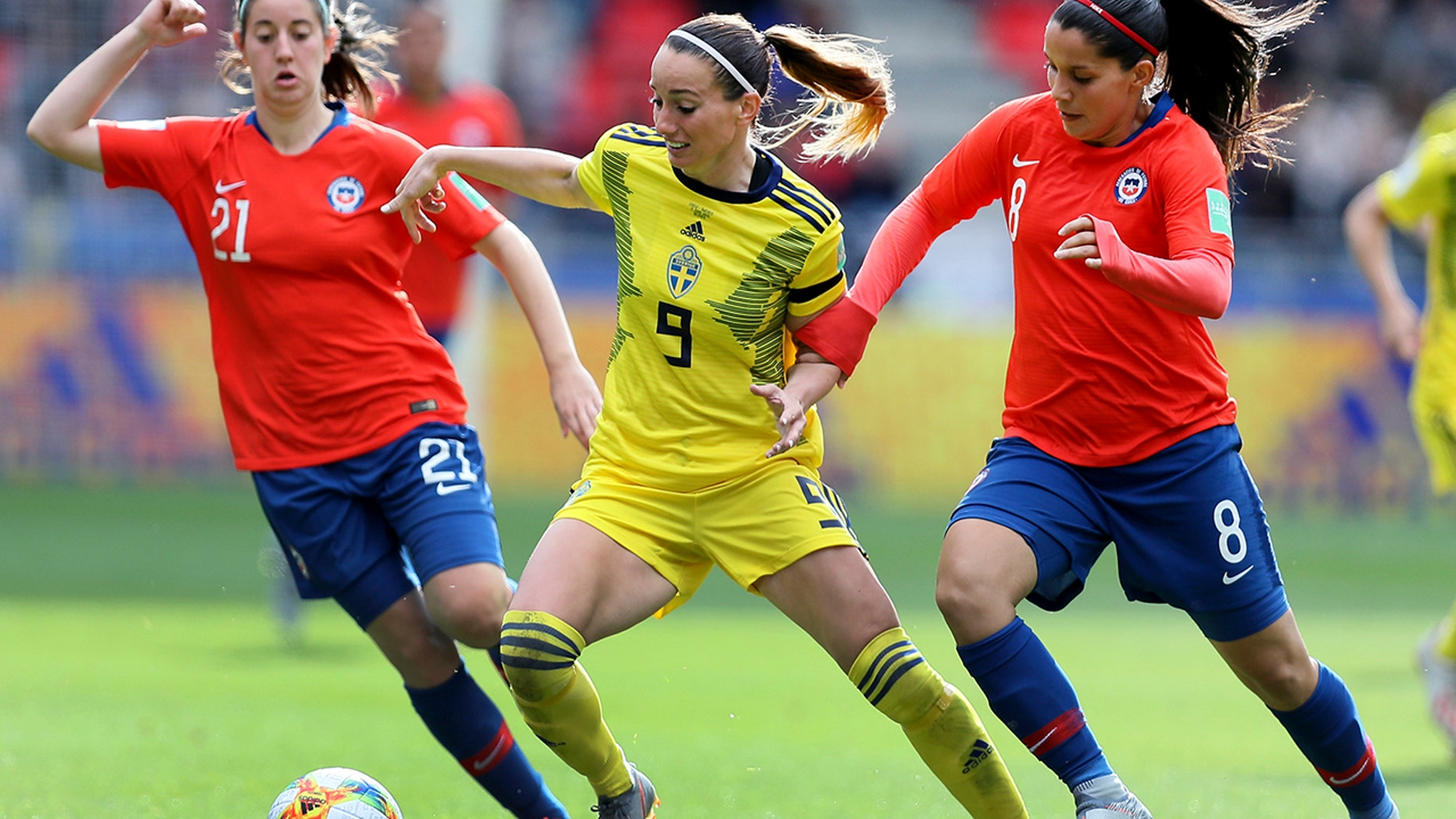 Sweden's Kosovare Asllani, center, and Chile's Karen Araya, right, plea for a round during a Women's World Cup Group F soccer compare between Chile and Sweden during a Roazhon Park in Rennes, France, Tuesday, Jun 11, 2019. (AP Photo/David Vincent)