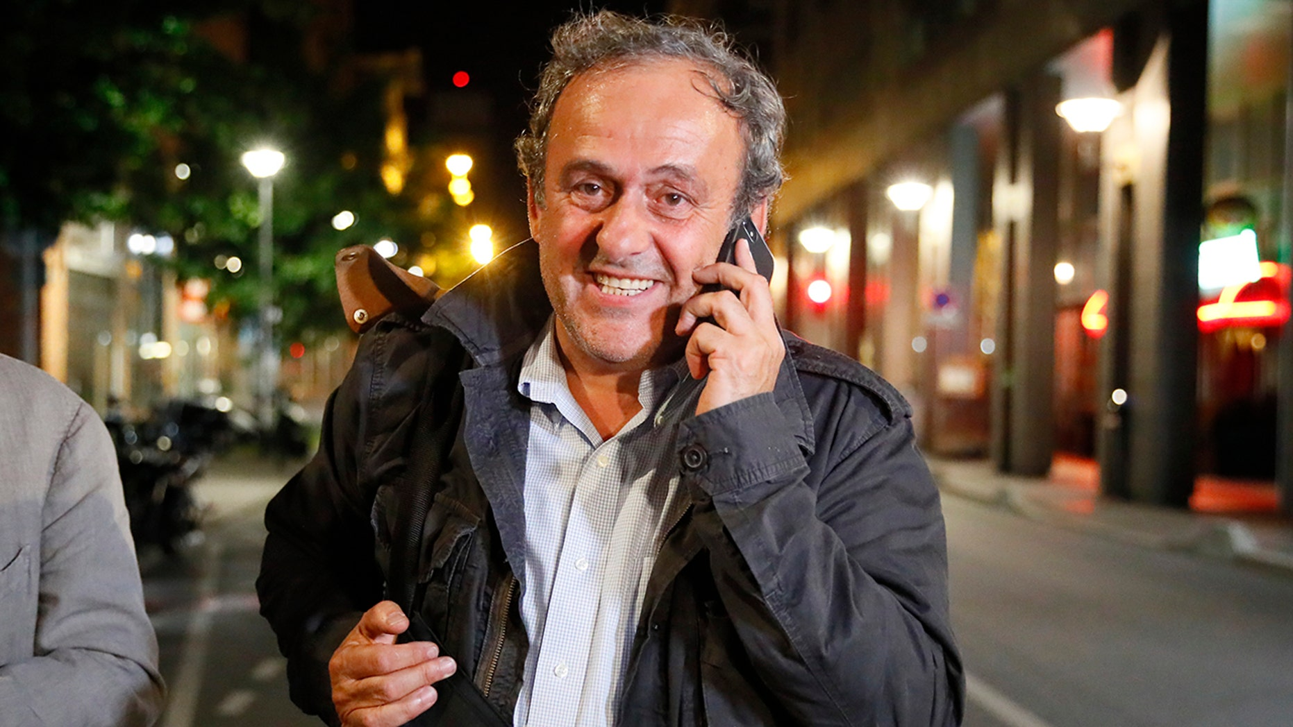 Michel Platini makes a phone call after being freed, outside the French police anti-corruption and financial crimes office in Nanterre, outside Paris, early Wednesday, June 19, 2019. Former UEFA president Michel Platini proclaimed his innocence during police questioning Tuesday following his arrest as part of a corruption probe into the vote that gave the 2022 World Cup to Qatar. (AP Photo/ Francois Mori)