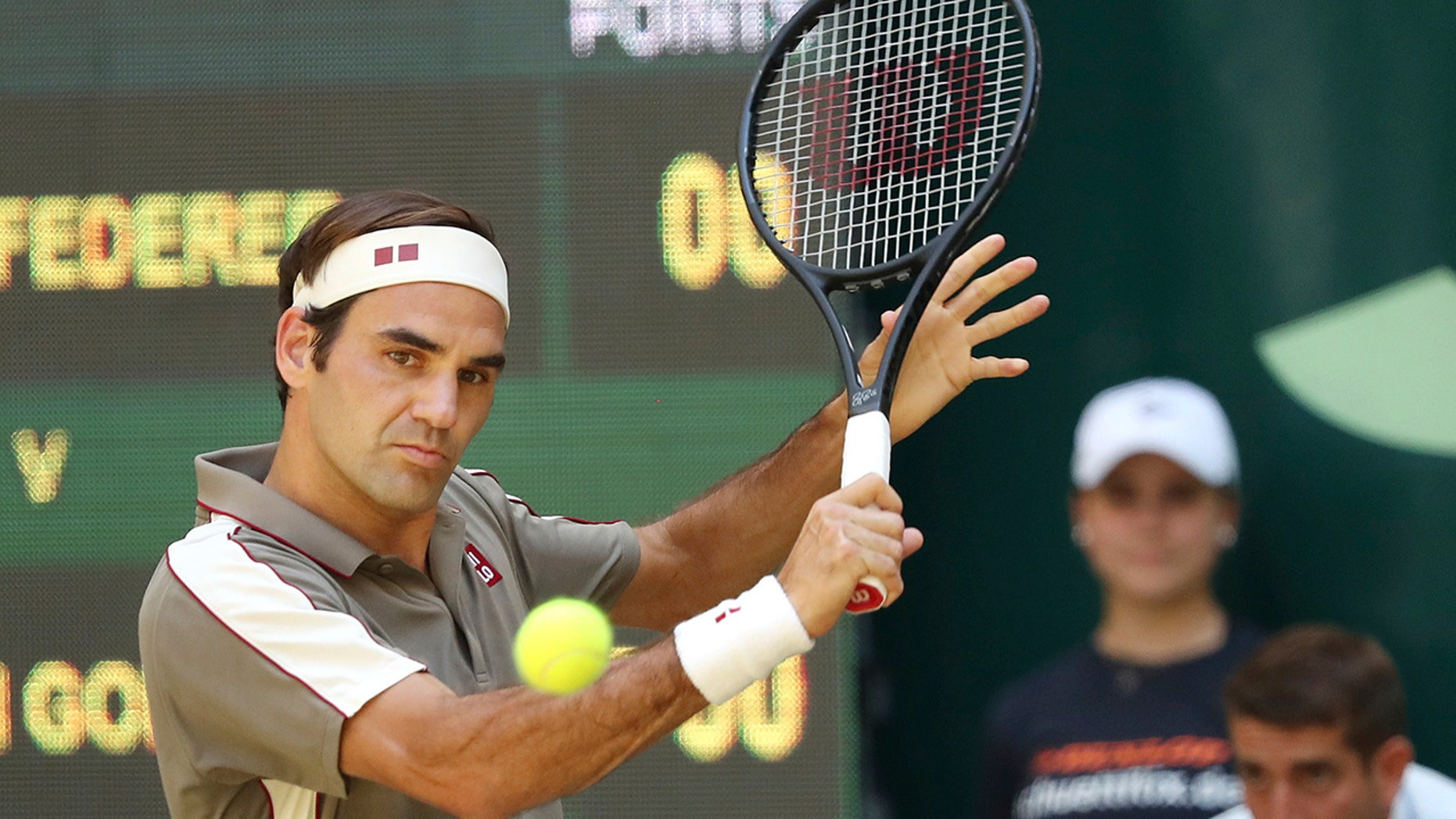 Swiss Roger Federer hits a backhand in the tennis ATP final against Belgium David Goffin in Halle, Germany, Sunday, June 23, 2019. (Friso Gentsch/dpa via AP)