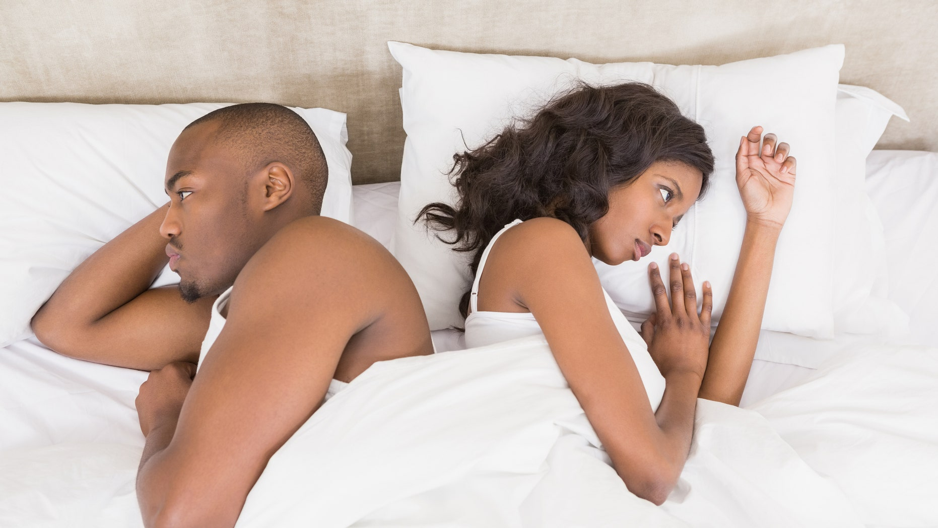Young couple back to back ignoring each other in the bedroom