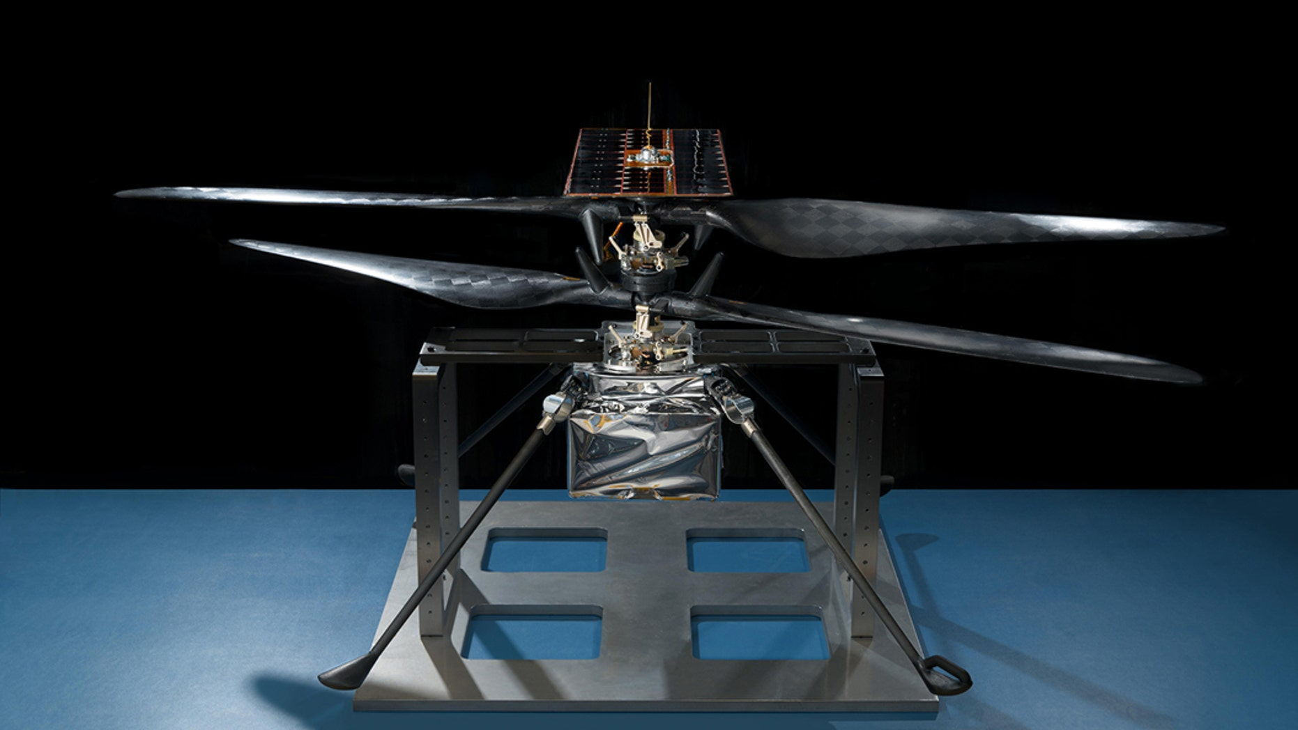 This image of the flight model of NASA's Mars Helicopter was taken on Feb. 14, 2019, in a cleanroom at NASA's Jet Propulsion Laboratory in Pasadena, California. The aluminum base plate, side posts, and crossbeam around the helicopter protect the helicopter's landing legs and the attachment points that will hold it to the belly of the Mars 2020 rover. (Credit: NASA/JPL-Caltech )