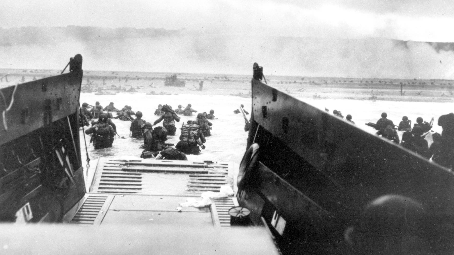 FILE - In this June 8, 1944, file photo, under heavy German machine gun fire, American infantrymen wade ashore off the ramp of a Coast Guard landing craft during the invasion of the French coast of Normandy in World War II. June 6, 2019, marks the 75th anniversary of D-Day, the assault that began the liberation of France and Europe from German occupation, leading to the end World War II.