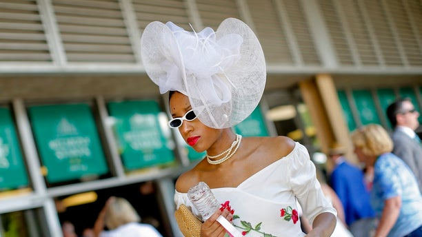 A spectator walks through the grandstand before the 151st running of the Belmont Stakes horse race, Saturday, June 8, 2019, in Elmont, N.Y. (AP Photo/Eduardo Munoz Alvarez)