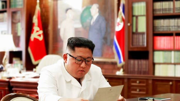FILE: North Korean leader Kim Jong Un reads a letter from U.S. President Donald Trump.