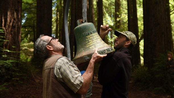 David Jessen, left, and Mitch Smith, both UC Santa Cruz employees, officially remove an El Camino Real bell marker from campus during a ceremony on Friday, June 21, 2019, in Santa Cruz, Calif. (AP Photo/Cody Glenn)