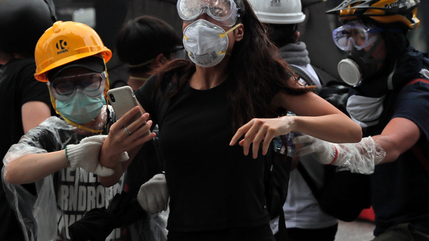Protesters flee after police fired tear gas during a massive demonstration outside the Legislative Council in Hong Kong on June 12, 2019. (AP Photo/Kin Cheung)