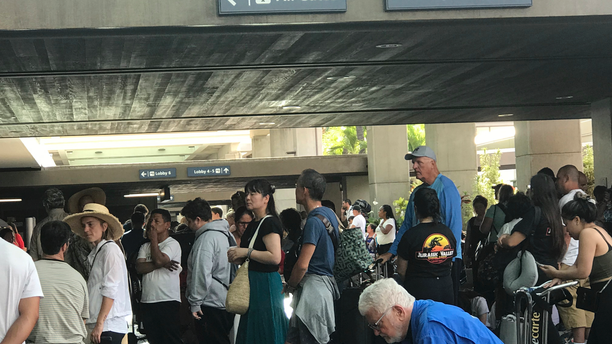 In this photo provided by Leslie Ryan, passengers jam the open air lobby at Terminal 2 at Daniel K. Inouye International Airport in Honolulu, Tuesday, June 18, 2019. Flights were being delayed and hundreds of people were waiting to go through security screening at Honolulu's airport after an active shooter scare. (Leslie Ryan via AP)