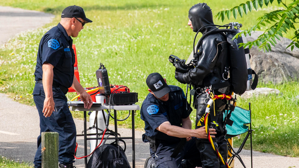 Police search the Kalamazoo River near Verburg Park, Tuesday, June 18, 2019, after finding the bodies of a mother and child inside a submerged vehicle, in Kalamazoo, Mich. Police believe a second child, who is missing, may also have been inside the vehicle when it entered the water late Monday evening. (Joel Bissell/Kalamazoo Gazette via AP)
