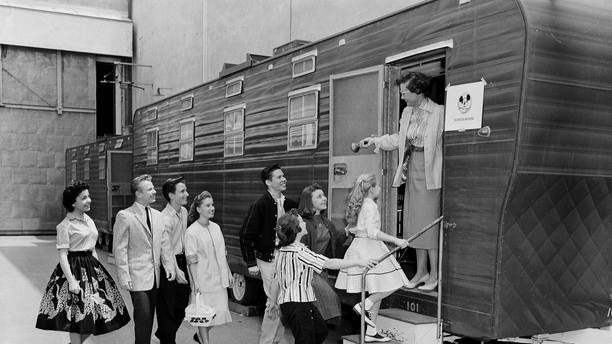 In this Aug 20, 1957, file photo, Walt Disney's Mouseketeers enter a large trailer that serves as their school on the Disney lot in Hollywood, Calif. Greeting them is their teacher Jean Seaman of the Los Angeles Public School System. Jimmy Dodd, red-haired and fortyish, is master of Mouseketeer ceremonies. Mouseketeer Annette Funicello can be seen at far left.