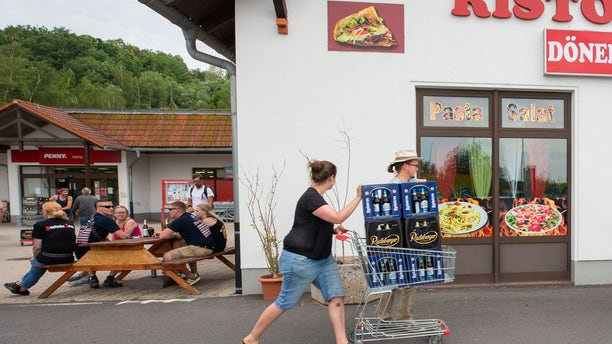 A woman and a man push a shopping cart with beer crates along the street near a local supermarket to protest theShield and Sword Festival. (Photo by Daniel Schäfer/picture alliance via Getty Images)