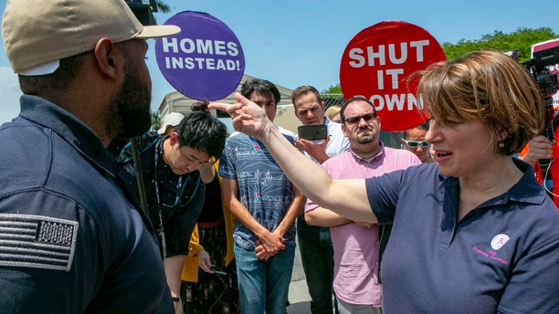 Democratic presidential candidate Amy Klobuchar requests to be let in into the Homestead Detention Center during a visit ahead of the first Democratic Debates, in Homestead, Fla. Wednesday June 26, 2019. (Daniel A. Varela/Miami Herald via AP)