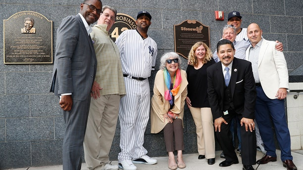 Representatives of the the Stonewall Inn and the New York Yankees, including pitcher CC Sabathia, third from left; relief pitcher Dellin Betances, second from right; assistant general manager Jean Afterman, center; and general manager Brian Cashman, right, honor the 50th anniversary of the Stonewall Inn Uprising after the Yankees unveiled a plaque in Monument Park before a baseball game Tuesday, June 25, 2019, in New York. (AP Photo/Kathy Willens)