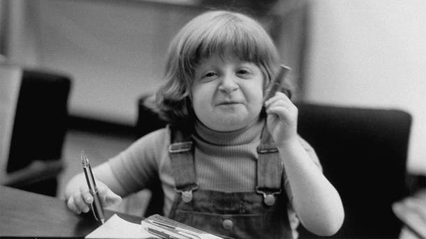 Child model Mason Reese seated at a table.