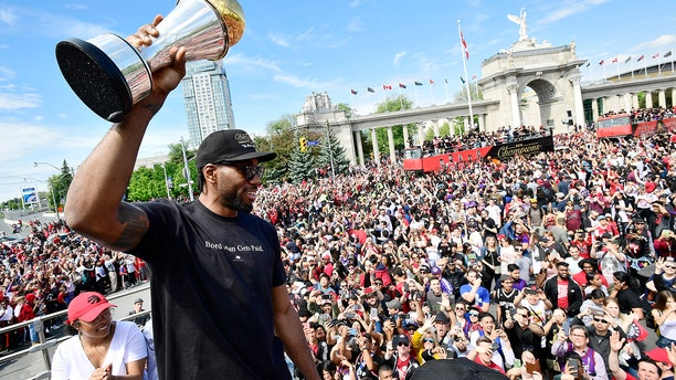 Toronto Raptors forward Kawhi Leonard holds his playoffs MVP trophy during the NBA basketball championship team's victory parade in Toronto, Monday, June 17, 2019. (Frank Gunn/The Canadian Press via AP)