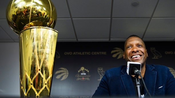 Toronto Raptors NBA basketball team president Masai Ujiri speaks to the media during an end-of-season press conference in Toronto, Tuesday, June 25, 2019. At left is the Larry O'Brien Trophy. (Nathan Denette/The Canadian Press via AP)