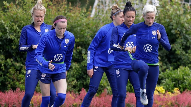 US player Megan Rapinoe, front right, stretches with Ali Krieger and other team members during a US women's soccer team training session at the Tottenham Hotspur training center in London (AP Photo/Kirsty Wigglesworth)