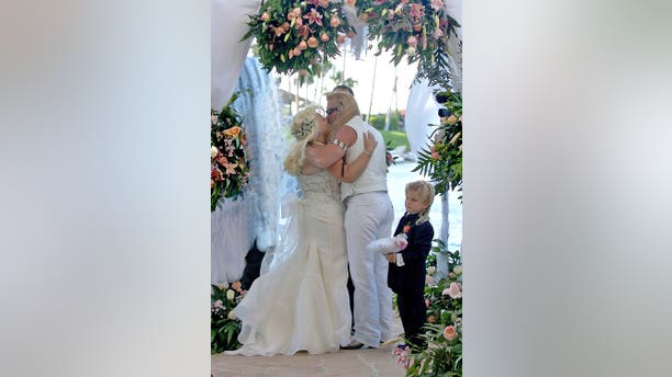 """Beth Chapman wife of Bounty Hunter Duane """"Dog"""" Chapman kiss under an archway of roses near the waterfall at the Hilton Waikoloa Village in Waikoloa, on the Big Island of Hawaii, May 20, 2006."""