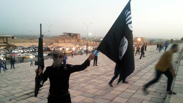 An ISIS fighter holds a flag and a weapon on a street in the city of Mosul in 2014.